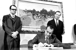 In this photograph from December 31, 1970, President Nixon signs the Clean Air Act as the first Environmental Protection Agency Administrator William Ruckelshaus and the Council on Environmental Quality Chairman Russell Train look on.