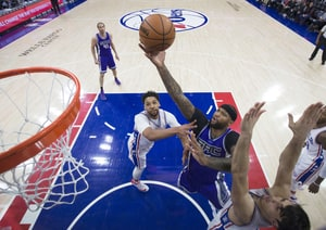 DeMarcus Cousins #15 of the Sacramento Kings attempts a shot against Jahlil Okafor #8 and Dario Saric #9 of the Philadelphia 76ers in the first quarter at the Wells Fargo Center on January 30, 2017 in Philadelphia, Pennsylvania.