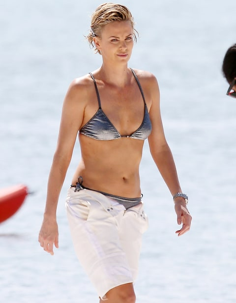 Onun uzun vücudu ve Koyu sarı saç stili sütyensiz (cup size 36B) plajda bikinili