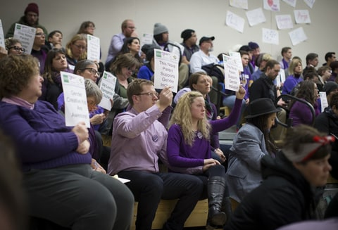 Dave and Hannah Edwards (in center holding hands), the parents of a gender nonconforming child at Nova Classical Academy, sat with signs in silent protest during a talk by Autumn Leva the Minnesota Family Council called Title IX and Gender Identity on Tuesday, January 12, 2015, in St. Paul, Minn.