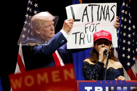 A woman joins Republican presidential nominee Donald Trump as he holds up a ''Latinas for Trump'' sign during a campaign rally at the Venetian Hotel in Las Vegas, Nevada, U.S. October 30, 2016.