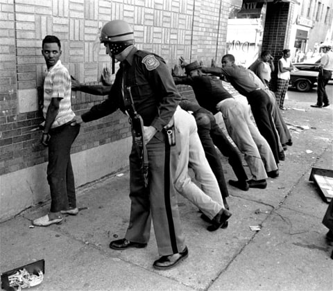 In this July 24, 1967 file photo, a Michigan State police officer searches a youth on Detroit's 12th Street where looting was still in progress after the previous day's rioting. The July 23, 1967 raid of an illegal after-hour's club, though, was just the spark. Many in the community blamed frustrations blacks felt toward the mostly white police, and city policies that pushed families into aging and over-crowded neighborhoods.