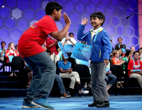 Six-year-old Akash Vukoti (R) of San Angelo, Texas, hi-fives Alex Iyer (L) of San Antonio, Texas, as he leaves the stage after he misspelled his word in round three of the 2016 Scripps National Spelling Bee May 25, 2016 in National Harbor, Maryland.