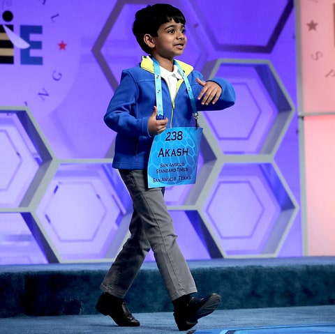 Six-year-old Akash Vukoti of San Angelo, Texas, approaches the microphone as he participates in round three of the 2016 Scripps National Spelling Bee May 25, 2016 in National Harbor, Maryland.
