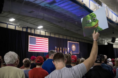 An attendee holds up a sign of Pepe the Frog, a cartoon tied to anti-Semitism and racism that has become an unofficial mascot of the alt-right, during a campaign event with Donald Trump at a sports complex in Bedford, N.H., Sept. 29, 2016. Secret Service agents later confiscated the sign.