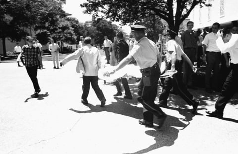 In this Aug. 1, 1966, file photo, one of the victims of Charles Whitman, the sniper who gunned down victims from a perch in the University of Texas tower, is carried across the campus to a waiting ambulance in Austin. The unidentified victim was gunned down inside the tower, according to police on the scene.