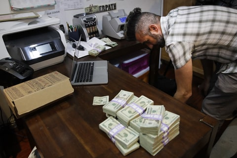 In this June 27, 2017, photo, bundles of $20 bills are placed on a table as Jerred Kiloh, owner of the Higher Path medical marijuana dispensary, prepares a trip to Los Angeles City Hall to pay his monthly tax payment in cash in Los Angeles. For Kiloh, the cash is a daily hassle. It needs to be counted repeatedly to safeguard against loss. State and local taxes must be set aside and stored, sometimes for a month or more. When vendors show up, they get paid in cash, too.