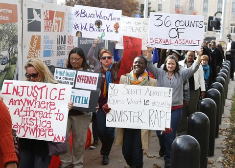 Protestors carry signs outside the courthouse as the jury deliberates in the trial of Daniel Holtzclaw, in Oklahoma City, Tuesday, Dec. 8, 2015. Holtzclaw is a former police officer accused of sexually victimizing 13 women in the neighborhood he patrolled.