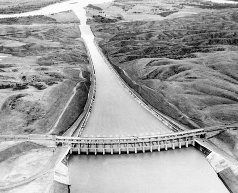 This Sept. 18, 1946 aerial view taken from a U.S. Army airplane flying over Fort Peck Lake, near Glasgow, Mont. shows operational tests of the mile-long concrete lined spillway of the Fort Peck Dam, the first of the U.S. Army Corps of Engineers' dams to be completed in the Missouri River basin. In the foreground is a structure, 800 feet wide and 86 high, which supports 16 floodgates. A $25 million, five-year study was authorized by Congress to determine whether changes need to be made in the 1944 law that sets eight purposes for the dams, reservoirs and lower free-flowing river: flood control, navigation, hydropower, irrigation, water supply, recreation, water quality, and fish and wildlife.