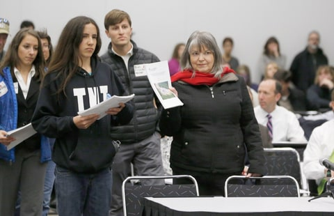 Anti-fracking activists led by Xiuhtezcatl Martinez, left, of Earth Guardians, and Karen Dike, a retired registered nurse from Longmont, Colo., present studies to members of the Oil and Gas Task Force as they meet to put the final touches on recommendations for Colorado Gov. John Hickenlooper to consider in the settlement of disputes over oil and gas drilling Tuesday, Feb. 24, 2015, in Denver. The meeting comes as some activists have renewed a campaign to banning the use of hydraulic fracturing in the state.
