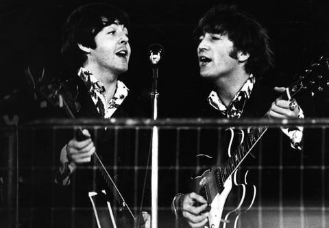 John Lennon and Paul McCartney of The Beatles share a microphone during the last concert on their final tour at Candlestick Park, San Francisco, California, August 29, 1966.
