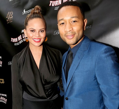 Chrissy Teigen and John Legend pose at the opening night of 'Turn Me Loose.'