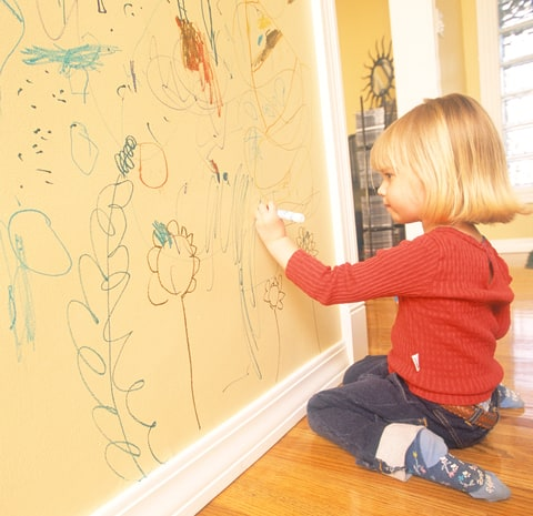 Little girl writing on the wall of her house.