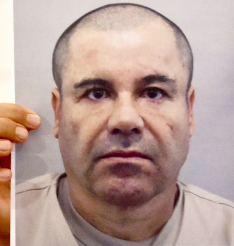 A man shows a picture of Mexican drug kingpin Joaquin