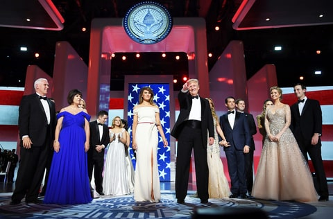 US President Donald Trump gestures as the first lady Melania Trump, Vice Presidant Mike Pence, his wife Karen and family look on at the Liberty Ball at the Washington DC Convention Center following Donald Trump's inauguration as the 45th President of the United States, in Washington, DC, on January 20, 2017.