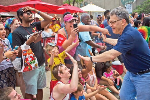 Minnesota Senator Al Franken greets spectators and participants at a Pride Parade in downtown Minneapolis, Minnesota.