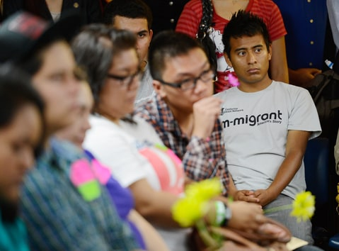 A group of immigrants, known as DREAMers, hold flowers as they listen to a news conference to kick off a new program called Deferred Action for Childhood Arrivals at the Coalition for Humane Immigrant Rights of Los Angeles on August 15, 2012 in Los Angeles, California.