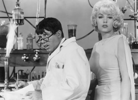 1963: American actor and comedian Jerry Lewis wearing a lab coat and glasses, as actor Stella Stevens poses next to him, in a still from Lewis's film, 'The Nutty Professor'.