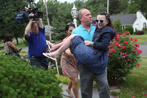 Justina Pelletier is carried into her home by her father, Lou. Justina was removed from her parents' care 16 months ago after allegations of medical child abuse were raised against Lou and Linda Pelletier.