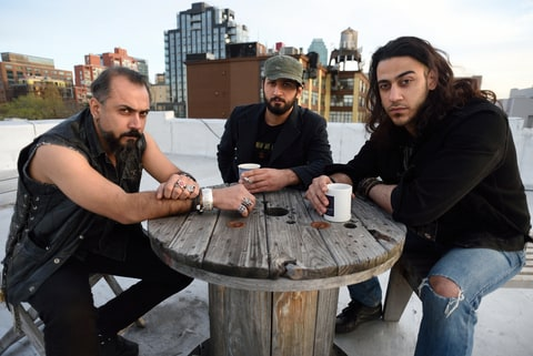 Members of the Iraqi heavy metal band Acrassicauda, (L to R) singer Faisal Mustafa, drummer and lyricist Marwan Hussein and guitarist Moe Al Hamawandi, pose for a photo on the roof of Spin Recording Studios April 30, 2015 in New York. The three Iraqi musicians have found a form of therapy not by firing guns but by banging their heads to heavy metal