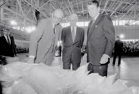 President Ronald Reagan (right) inspects a pile of confiscated cocaine 11/17 with U.S. Attorney General William F. Smith (center) and South Florida Task Force on Crime director Charles Rinkezich (left). President Reagan also viewed in the airplane hangar a stack of baled marijuana and aircraft used by government agencies to catch drug smugglers.