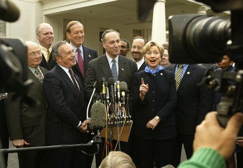 Holding a press conference outside of the White House are New York senator Charles Schumer, New York Governor George Pataki, New York City mayor Michael Bloomberg, and New York senator Hillary Clinton. The group are thanking President George Bush for supporting a $21.4 billion September 11 recovery package for their state.