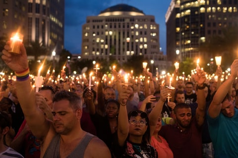 People hold candles during an evening memorial service for the victims of the Pulse Nightclub shootings, at the Dr. Phillips Center for the Performing Arts, June 13, 2016 in Orlando, Florida. The shooting at Pulse Nightclub, which killed 49 people and injured 53, is the worst mass-shooting event in American history.