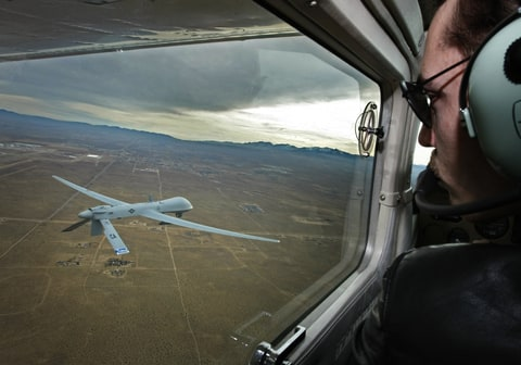 lot Mark Bernhardt keeps an eye a Predator unmanned drone from his chase plane as they fly over Victorville, CA, on January 9, 2010.