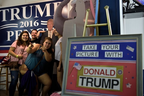 Women pose with a cardboard cutout of Donald Trump at the Shenandoah County Fair in Woodstock, Virginia.