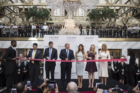 Republican presidential candidate Donald Trump, accompanied by, from left, Donald Trump Jr., Eric Trump, Trump, Tiffany Trump, Melania Trump, and Ivanka Trump, prepare to cut a ribbon during the grand opening ceremony of the Trump International Hotel- Old Post Office in Washington, DC on Wednesday October 26, 2016.