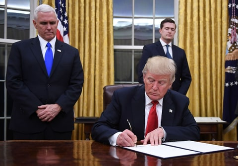 US President Donald Trump signs an executive order as Vice President Mike Pence looks on at the White House in Washington, DC on January 20, 2017,