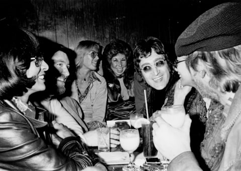Singer-guitarist John Lennon (center right), formerly of The Beatles, attends a Smothers Brothers comedy performance with girlfriend May Pang and fellow singer-songwriter Harry Nilsson (far right), during Lennon's infamous 'Lost Weekend' period, at the Troubadour on March 12, 1974, in West Hollywood, California. Lennon and Nilsson would later be kicked out of the show for drunken heckling.