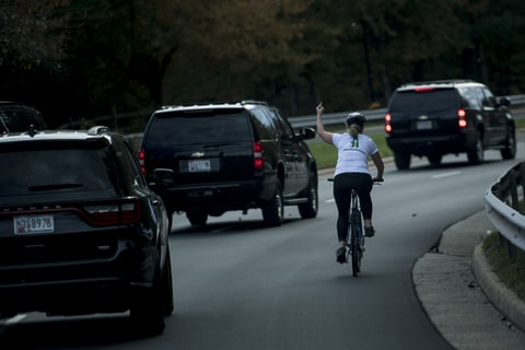 A woman on a bike gestures with her middle finger as a motorcade with US President Donald Trump departs Trump National Golf Course October 28, 2017 in Sterling, Virginia. / AFP PHOTO / Brendan Smialowski