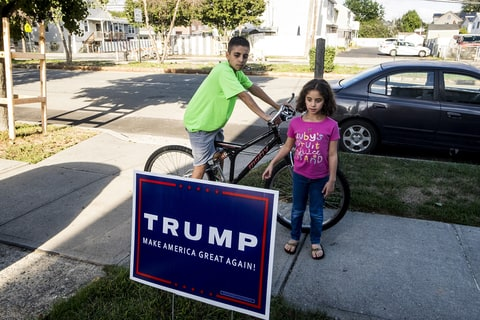 Abubeckr Elcharfa, 13, and his sister Maaria, 7, look at a neighbor's Donald Trump yard sign near their home on Staten Island in New York, Oct. 4, 2016. On the bus after school, a classmate once said to Abubeckr,