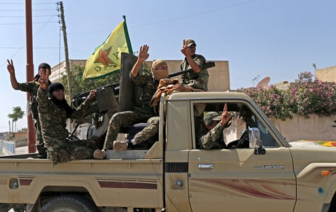 Members of Kurdish People Defence Units (YPG) flash victory sign after coming from Syrian town of al-Raqqa, in Tel Abyad, Syria, 23 June 2015. Kurdish fighters backed by US-led airstrikes captured a strategic town from Islamic State on 23 June
