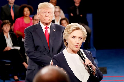 Democratic presidential nominee former Secretary of State Hillary Clinton (R) speaks as Republican presidential nominee Donald Trump looks on during the town hall debate at Washington University on October 9, 2016 in St Louis, Missouri.