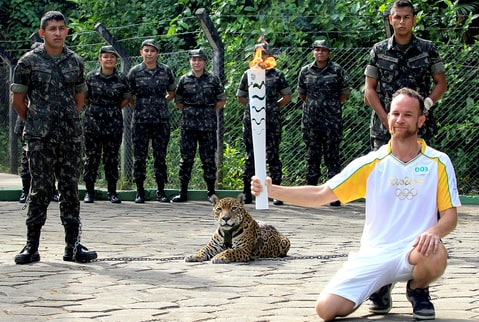 Brazilian physiotherapist Igor Simoes Andrade poses for picture next to jaguar Juma as he takes part in the Olympic Flame torch relay in Manaus, Brazil, June 20, 2016.