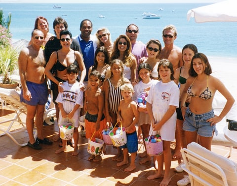 The Kardashian family poses with O.J. Simpson and Nicole Brown Simpson's family in Cabo San Lucas, Mexico in 1994.