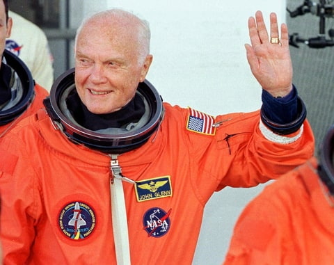 U.S. astronaut and senator John Glenn waves as he leaves the operations and checkout building at the Kennedy Space Center in Florida on October 29, 1998, en route to board Space Shuttle 'Discovery.'