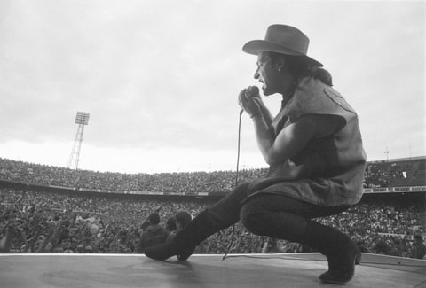 Bono performing live onstage at De Kuip stadium on The Joshua Tree tour, from stage, showing crowds of fans in stadium