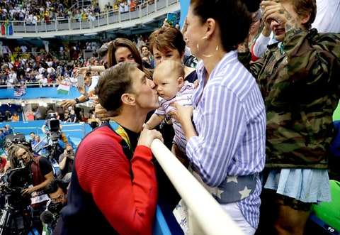United States' Michael Phelps celebrates winning his gold medal in the men's 200-meter butterfly with his mother Debbie, fiance Nicole Johnson and baby Boomer during the swimming competitions at the 2016 Summer Olympics, Tuesday, Aug. 9, 2016, in Rio de Janeiro, Brazil.