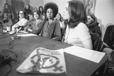1970 - Forty-six women employees of male-dominated Newsweek magazine conduct a press conference here March 16 to announce they are suing the magazine under the 1964 Civil Rights Act. Charging discrimination in jobs and hiring, they said they are 'forced to assume a subsidiary role simply because of their sex.' Seated (Left to Right) are: employees Patricia Lynden, Mary Pleshette, Eleanor Holmes Norton and ACLU legal director Lucy Howard.