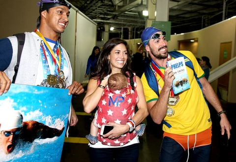 Nicole Johnson, fiancée of Michael Phelps, holding their baby son Boomer Phelps pose with fans of Phelps on day 8 of the Rio 2016 Olympic Games at Olympic Aquatics Stadium on August 13, 2016 in Rio de Janeiro, Brazil.