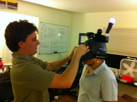 Palmer Luckey places a prototype Oculus Rift Razer Hydra VR helmet onto a Survios founder's head