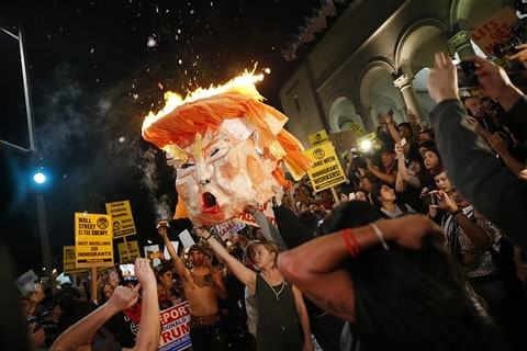 Image result for free photos or pictures of protesters burning American flag, or effigies of Donald Trump