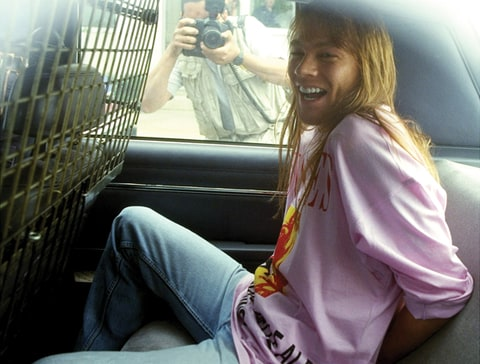 Axl Rose of Guns N' Roses sits handcuffed in the back of a police car.