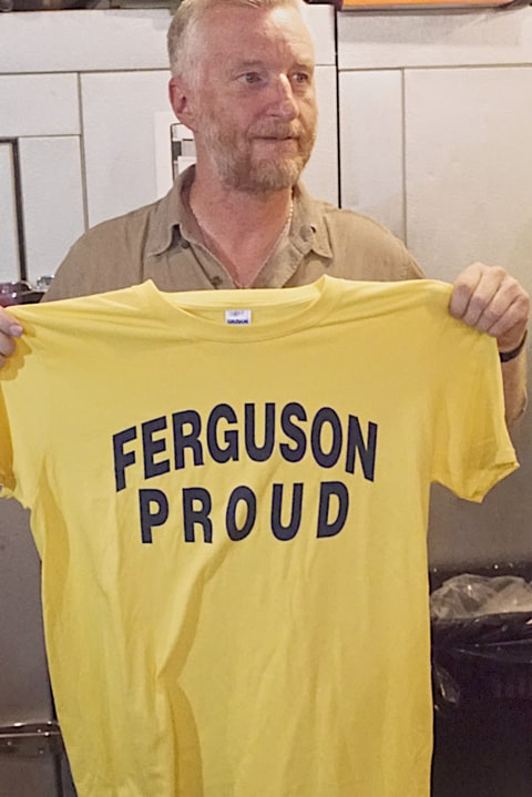 Billy Bragg holds up 'Ferguson Proud' t-shirt