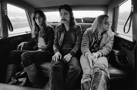 Rush posed sitting in a car in Birmingham, England during their 'Farewell To Kings' tour on 12th February 1978.