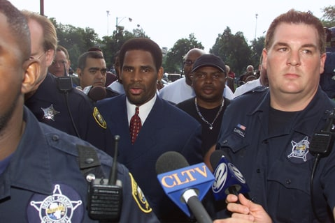 Grammy-winning singer R. Kelly (C) is surrounded by sheriff's deputies and the media as he is escorted into Cook County Circuit Court in Chicago, Illinois June 25, 2002. Kelly pleaded innocent to 21 counts of child pornography.