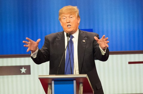Republican Presidential candidate Donald Trump (C) responds to a point during the Republican Presidential Debate in Detroit, Michigan